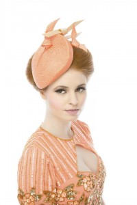 A small, neat, clean lined fascinator in a vibrant coral finished with floating hand sculpted knots of parasisal. Photographed by Ginny Marsh Photography.