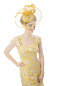 Laser cut Perspex wide brimmed saucer with natural centre and trimmed with mustard yellow Sinamay bind and twist detail. Photographed by Ginny Marsh Photography.